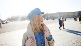 Stylish young blonde in denim cap and beige raincoat. Beautiful young woman stock photos