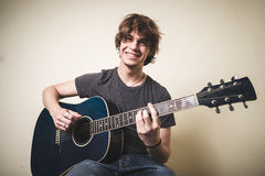 Stylish young blonde hipster man playing guitar. On white background Royalty Free Stock Image