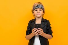 Stylish Young Boy In Black Jacket And White T-shirt Serfing Internet With His Phone Stock Image