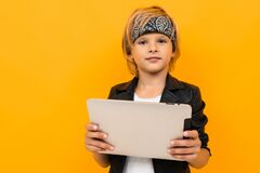 Stylish Young Boy In Black Jacket And White T-shirt Serfing Internet With His Tablet Stock Photography