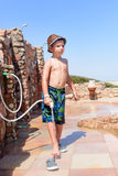 Stylish young boy rinsing off his feet. Stylish young boy in a swimsuit and trendy hat standing rinsing off his feet with a hosepipe after visiting the beach at Royalty Free Stock Photo