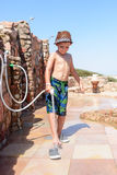 Stylish young boy rinsing off his feet. Stylish young boy in a swimsuit and trendy hat standing rinsing off his feet with a hosepipe after visiting the beach at Stock Photography