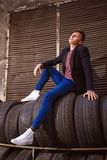 Brunet. Stylish young brunet in leather jacket standing near wall Royalty Free Stock Photos