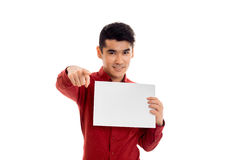 Stylish young brunette male model in red t-shirt posing with empty placard in his hands smiling on camera isolated on Royalty Free Stock Photos