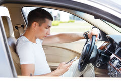 Stylish young brunette man uses the phone in the car Royalty Free Stock Photos