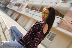 Stylish young brunette woman in sunglasses sitting Stock Photo
