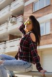 Stylish young brunette woman in sunglasses sitting Stock Images