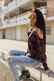Stylish young brunette woman in sunglasses sitting Royalty Free Stock Image