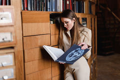 Stylish young business lady in glasses reads a book at the library Royalty Free Stock Images
