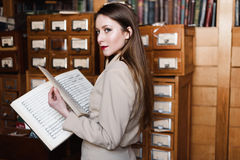 Stylish young business lady in glasses reads a book at the library Stock Photography