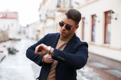 Stylish young businessman in an elegant coat in trendy sunglasses with a stylish hairstyle in a knitted sweater looks at a hand. On the background of vintage stock images