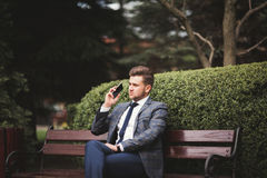 Stylish young businessman talking on the phone outdoors Royalty Free Stock Image