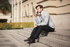 Stylish young businessman talking on the phone outdoors Royalty Free Stock Images