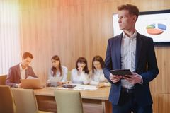 Stylish young businessman wearing a jacket and a shirt on the background of a working office with people working with a tablet royalty free stock photo