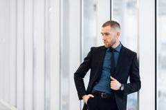 Stylish young businessman wearing a modern suit, who is a high achiever, standing on the top floor of an office building royalty free stock photo