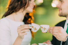 Stylish young couple enjoying tea time in the green garden Stock Photos