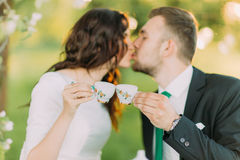 Stylish young couple kiss during tea time in the green garden Royalty Free Stock Photography