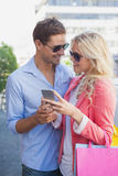 Stylish young couple looking at smartphone holding shopping bags Royalty Free Stock Photos