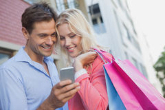Stylish young couple looking at smartphone holding shopping bags Stock Photos