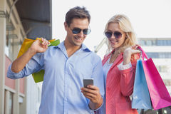Stylish young couple looking at smartphone holding shopping bags Royalty Free Stock Photography