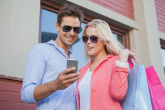 Stylish young couple looking at smartphone holding shopping bags Stock Photo