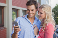 Stylish young couple looking at smartphone Royalty Free Stock Image