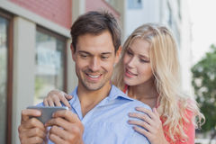 Stylish young couple looking at smartphone Royalty Free Stock Photo
