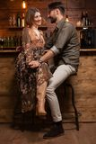 Stylish young couple on a night out in a vintage pub and holding hands royalty free stock photography