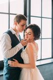 Stylish young couple posing against the backdrop of a luxurious interior. The groom hugs the bride`s waist. Fine`s Photo Royalty Free Stock Photos