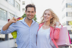 Stylish young couple smiling at camera holding shopping bags Stock Photo