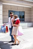 Stylish Young Couple Walking With Shopping Bags On A Sunny Day. Beautiful young couple in love going on a shopping spree in the city on a sunny day Royalty Free Stock Photo