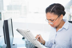 Stylish young dark haired businesswoman reading a newspaper Royalty Free Stock Image