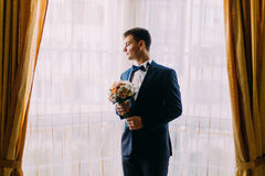 Stylish young dark haired groom holding a wedding bouquet of pale pink roses in hands standing near the window Royalty Free Stock Image