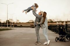 Stylish young family dressed in denim clothes walks near the river with a stroller