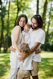 Stylish young family is having rest in the park. Dad and mom are holding daughter in the arms and hugging son. royalty free stock image