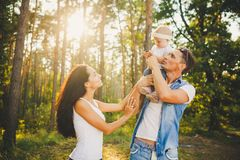 Stylish young Family mom, dad and daughter one year old blonde sitting with father on shoulders playing happy and smiling, outdoor Stock Photography