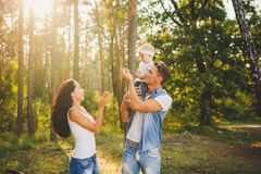 Stylish young Family mom, dad and daughter one year old blonde sitting with father on shoulders playing happy and smiling, outdoor Royalty Free Stock Photo