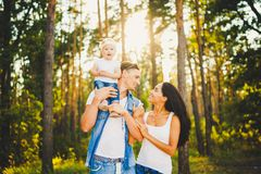 Stylish young Family of mom, dad and daughter one year old blonde sitting near father on shoulders, outdoors outside the city in a Royalty Free Stock Image