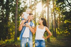 Stylish young Family of mom, dad and daughter one year old blonde sitting near father on shoulders, outdoors outside the city in a Stock Photo
