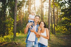 Stylish young Family of mom, dad and daughter one year old blonde sitting near father on shoulders, outdoors outside the city in a Royalty Free Stock Photo