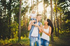 Stylish young Family of mom, dad and daughter one year old blonde sitting near father on shoulders, outdoors outside the city in a Stock Photos