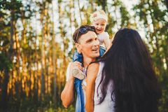 Stylish young Family of mom, dad and daughter one year old blonde sitting near father on shoulders, outdoors outside the city in a Royalty Free Stock Photography