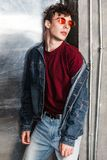 Stylish young fashion model man in bright red sunglasses and denim casual style posing near metallic door, lean and looking at. Camera with serious face. indoor royalty free stock photography