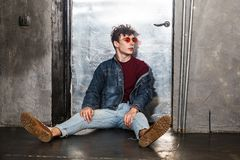 Stylish young fashion model man in bright red sunglasses and denim casual style sitting on floor and posing near metallic door and. Looking away. indoor, studio royalty free stock photos