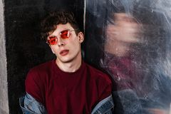 Stylish young fashion model man in bright red sunglasses and denim casual style sitting on floor and posing near metallic door and. Looking at camera. indoor royalty free stock photo
