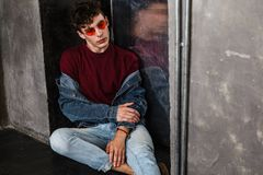 Stylish young fashion model man in bright red sunglasses and denim casual style sitting on floor and posing near metallic door and. Looking away. indoor, studio stock photo