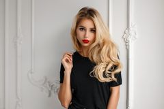 Stylish young fashionable blond woman with a hairdo in a trendy. Black t-shirt near a white vintage wall royalty free stock images