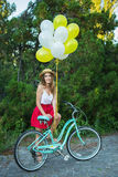 Stylish young female with a bicycle in park. Girl enjoying a day on bike Royalty Free Stock Photography