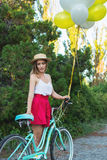 Stylish young female with a bicycle in park. Girl enjoying a day on bike Stock Photography