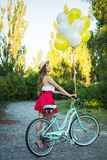 Stylish young female with a bicycle in park. Girl enjoying a day on bike Stock Photos
